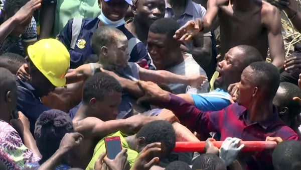 In this image taken from video, people help a child after he was rescued from the scene of a building collapse