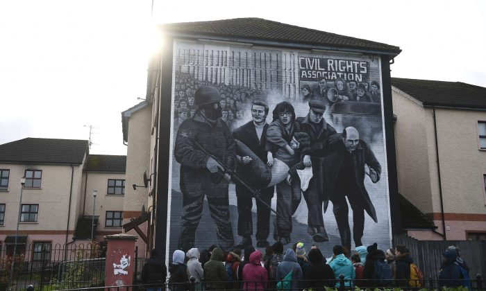Tourists stand in front of a mural depicting Bloody Sunday, in Londonderry, Northern Ireland, on March 14, 2019. (Clodagh Kilcoyne/Reuters)