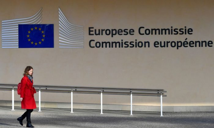 A woman walks past the entrance of the European Commission in Brussels on Nov. 14, 2018. (Emmanuel Dunand/AFP/Getty Images)