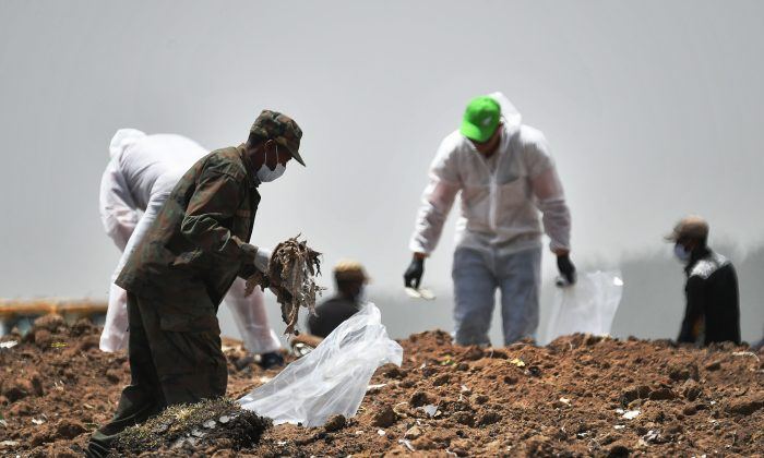 Forensics experts comb through the dirt for debris at the crash site of the Ethiopian Airlines operated Boeing 737 MAX aircraft, at Hama Quntushele village in Oromia region, on March 14, 2019, four days after the plane crashed into a field killing 157 passengers and crew. (Tony Karumba/AFP/Getty Images)