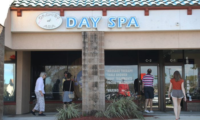 People mill around in front of the Orchids of Asia Day Spa in Jupiter, Florida, on Feb. 22, 2019. The former owner of the spa was recently revealed to have sought out opportunities to network with Republican Party politicians. (Joe Raedle/Getty Images)