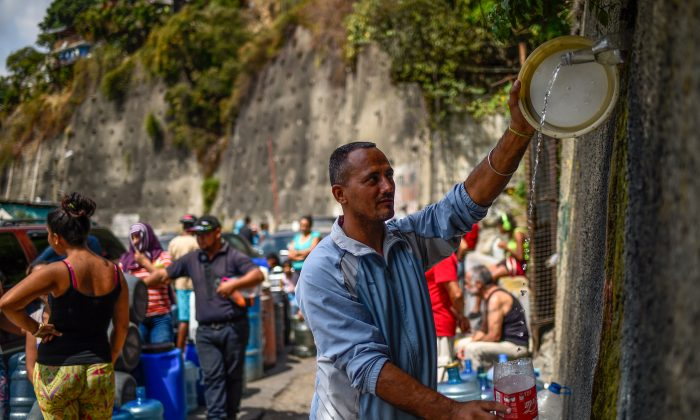 "A man fills containers with water flowing down from the Wuaraira Repano mountain, also called ""El Avila"", in Caracas on March 13, 2019. Millions in Venezuela have been left without running water.(Federico Parra/AFP/Getty Images)"
