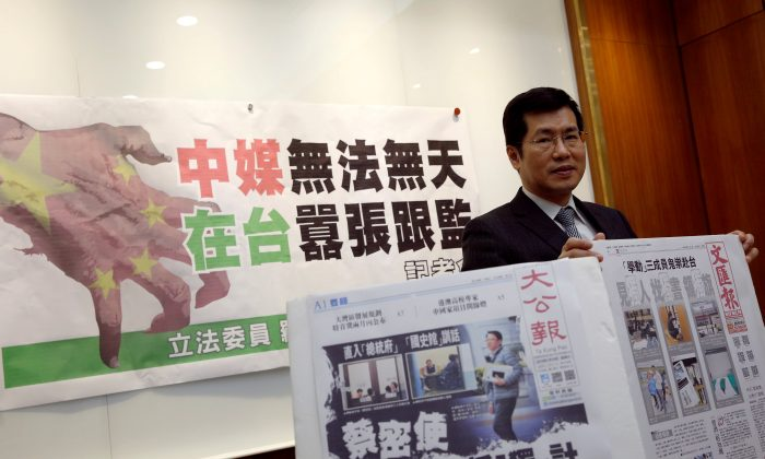 Democratic Progressive Party lawmaker Lo Chih Cheng poses with copies of Hong Kong's Ta Kung Pao and Wen Wei Po newspapers after a news conference in Taipei, Taiwan on Jan. 18, 2019. (Tyrone Siu/Reuters)