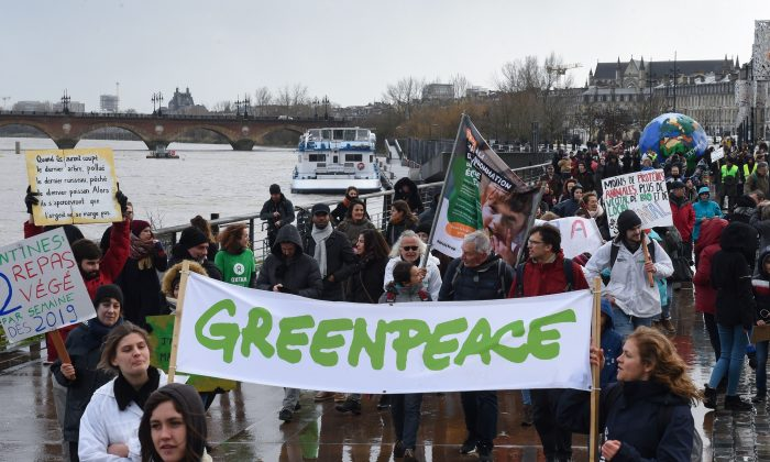 "People hold a banner reading ""Greenpeace"" as they take part in a march for the climate, in Bordeaux, on January 27, 2019. MEHDI FEDOUACH/AFP/Getty Images"