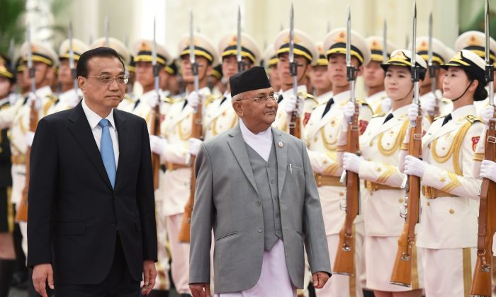 Nepal's Prime Minister K.P. Sharma Oli reviews a military honour guard with Chinese Premier Li Keqiang during a welcome ceremony at the Great Hall of the People in Beijing on June 21, 2018. (Greg Baker/AFP/Getty Images)