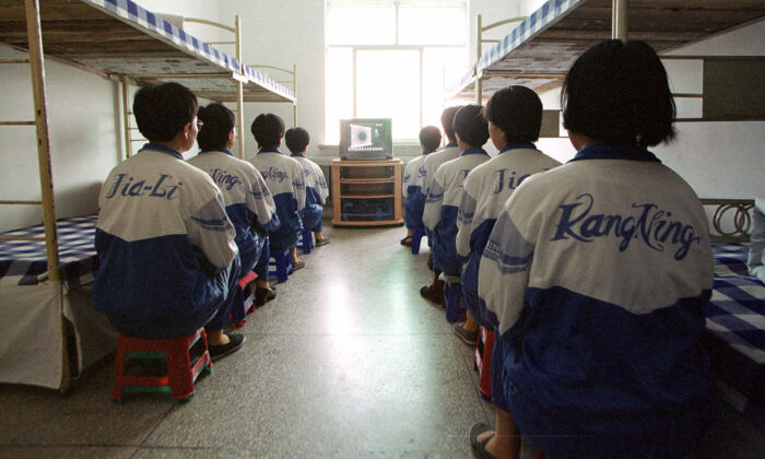 "Falun Dafa practitioners are shown in the Masanjia labour camp watching a video meant to ""re-educate"" them during a propaganda tour arranged by the camp authorities on May 22, 2001. (AP Photo/John Leicester)"
