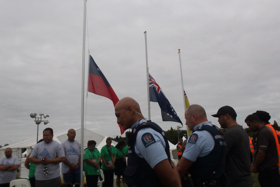 People gather around flags at half-mast