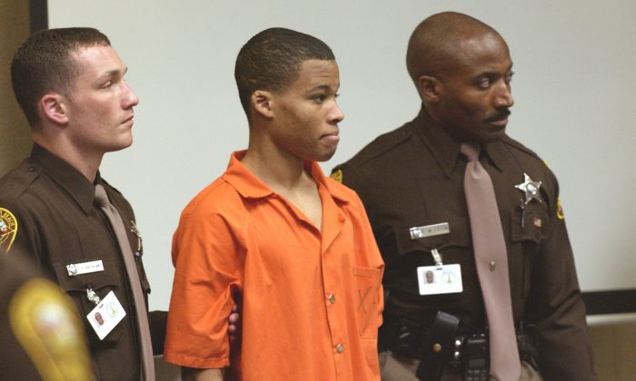 Sniper suspect Lee Boyd Malvo (C) is escorted by deputies as he is brought into court to be identified by a witness during the murder trial in courtroom 10 at the Virginia Beach Circuit Court in Virginia Beach, Virginia on Oct. 22, 2003.  (Davis Turner-Pool/Getty Images)