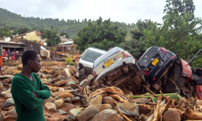 A man stands next to wrecked vehicles on March 18, 2019, in Chimanimani, eastern Zimbabwe, after the area was hit by Cyclone Idai. (Zinyange Auntony/AFP/Getty Images)