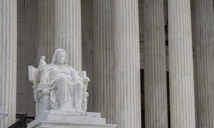 A statue outside the Supreme Court of the United States that stands for the contemplation of justice in Washington on Sept. 22, 2017. (Samira Bouaou/The Epoch Times)