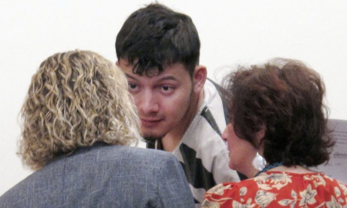 Wilber Ernesto Martinez-Guzman, 19, of El Salvador, talks to his public defender and interpreter during his initial appearance in Carson City Justice Court in Carson City, Nev., on Jan. 24, 2019. (Scott Sonner/AP Photo)