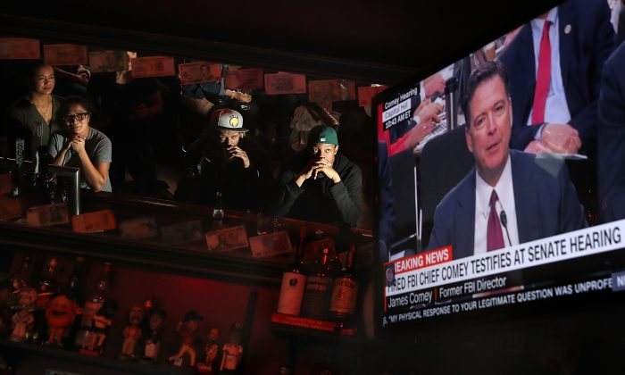 Patrons at Ace's Bar watch a television broadcast of former FBI Director James Comey testify before the Senate Intelligence Committee on June 8, 2017 in San Francisco, United States.  Justin Sullivan/Getty Images