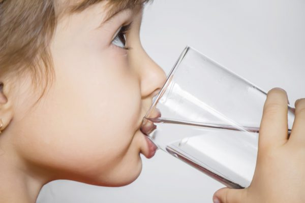 child holds a glass of water
