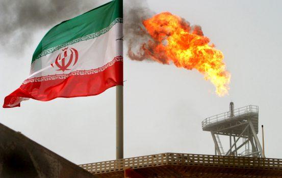 Une fusée éclairante sur une plate-forme de production pétrolière dans les gisements de Soroush côtoie un drapeau iranien dans le Golfe