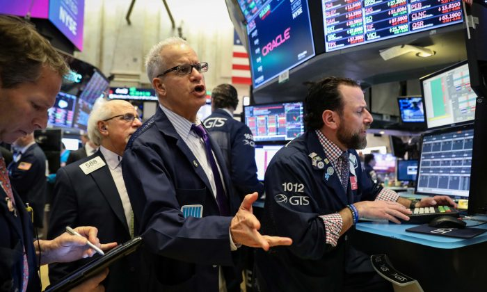 Traders work on the floor at the New York Stock Exchange (NYSE) in New York, U.S., March 22, 2019. REUTERS/Brendan McDermid