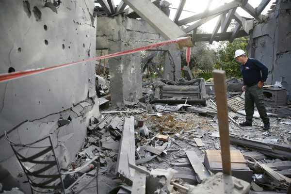 A police officer inspects the damage to a house hit by a rocket in Mishmeret central Israel