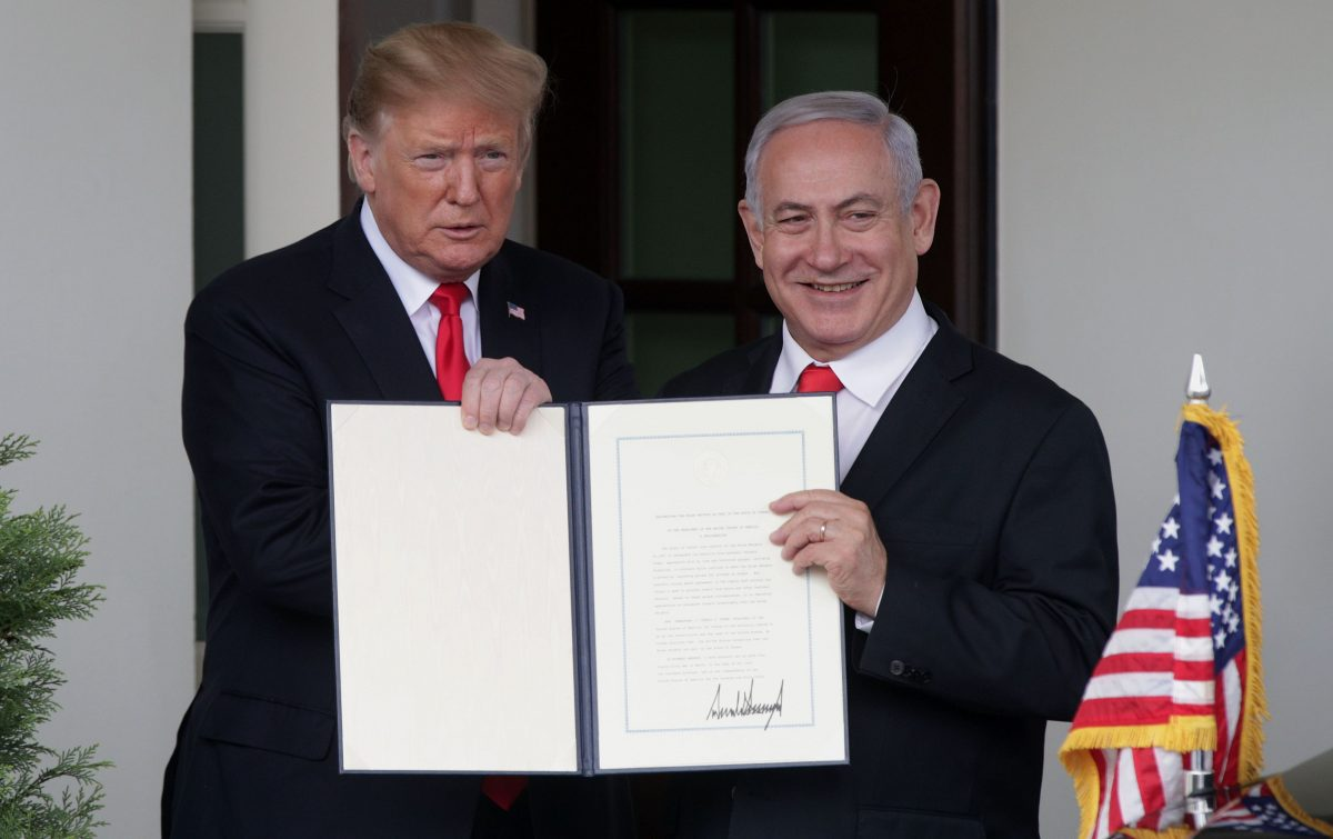 President Donald Trump (L) and Prime Minister of Israel Benjamin Netanyahu show the proclamation recognizing Israel's sovereignty over Golan Heights after a meeting outside the West Wing of the White House