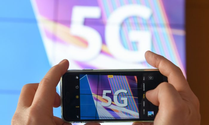 A journalist takes pictures of a projection screen prior to the start of Germany's auction for the construction of an ultra-fast 5G mobile network on March 19, 2019 at the German Federal Network Agency in Mainz, western Germany. (Arne Dedert/AFP/Getty Images)