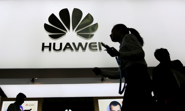People walk past a sign board of Huawei at CES (Consumer Electronics Show) Asia 2016 in Shanghai, China on May 12, 2016. (Aly Song/Reuters)