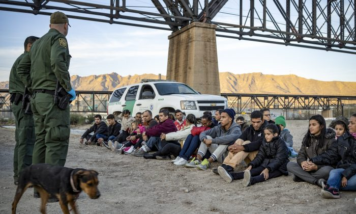 A group of about 30 Brazilian illegal immigrants, who had just crossed the border, sit on the ground near Border Patrol agents, on the property of Jeff Allen, on the U.S.–Mexico border in Sunland Park, New Mexico, on March 20, 2019. (Paul Ratje/AFP/Getty Images)
