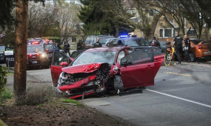 Police work the scene where two cars collided in Seattle, Wednesday, March 27, 2019, after a gunman opened fire on vehicles in a Seattle neighborhood. (Steve Ringman/The Seattle Times via AP)