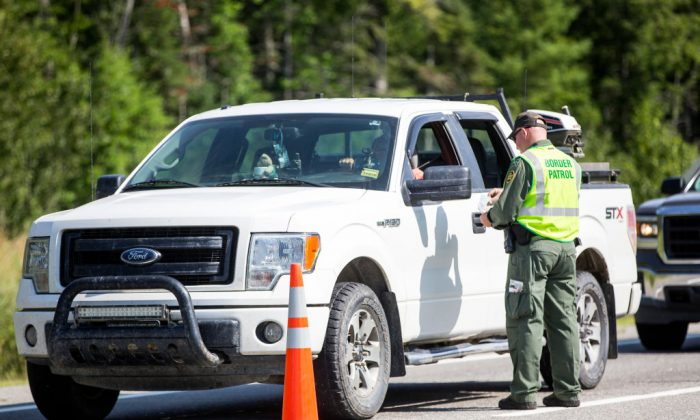 A U.S. Border Patrol agent checks identification of a driver at a highway checkpoint in West Enfield, Maine, on Aug. 1, 2018. (Scott Eisen/Getty Images)
