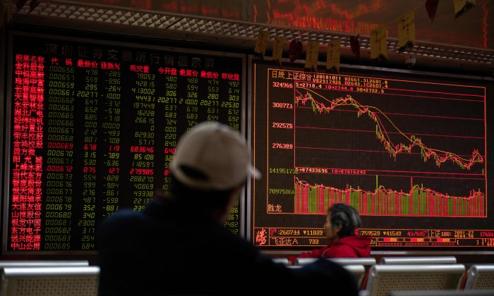 Investors look at stock price movements on a screen at a securities company in Beijing on October 11, 2018. (NICOLAS ASFOURI/AFP/Getty Images)