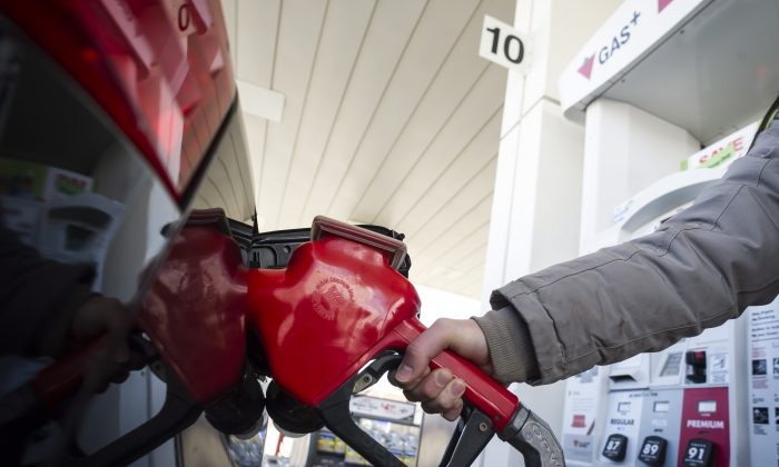 A woman fills up in Toronto on April 1, 2019. Gas prices rose by 4.42 cents a litre with the introduction of the federal carbon tax on that day. (The Canadian Press/Christopher Katsarov)