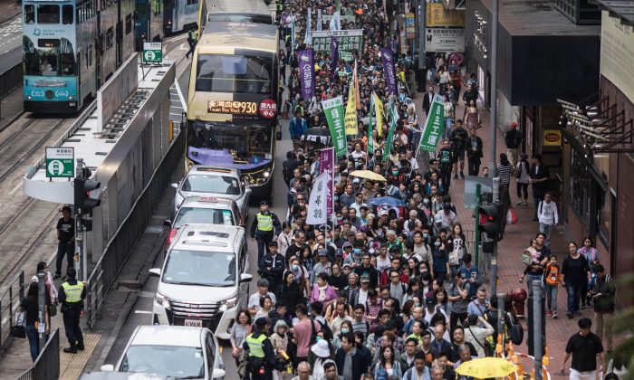 Protesters march along a street during a rally in Hong Kong on March 31, 2019 to protest against the government's plans to approve extraditions with mainland China, Taiwan and Macau. - Critics fear any extradition agreement could leave both business figures and dissidents in Hong Kong vulnerable to China's politicised courts, fatally undermining a business hub that has thrived off its reputation for a transparent and independent judiciary. (Photo by Dale DE LA REY / AFP)        (Photo credit should read DALE DE LA REY/AFP/Getty Images)