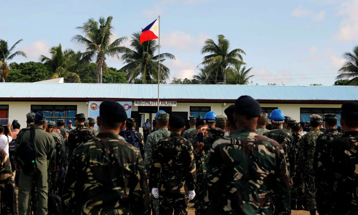 A Philippine flag flutters in Philippine occupied (Pagasa) Thitu island, in disputed South China Sea, as soldiers and civilians sing the country's national anthem on April 21, 2017. (Erik De Castro/Reuters)