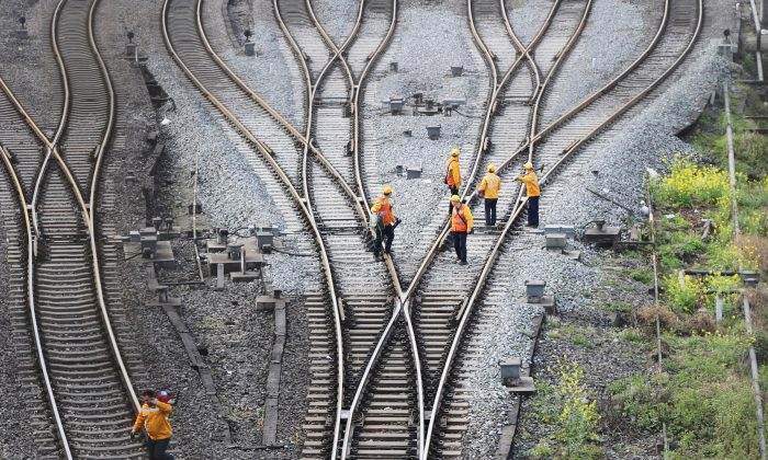 """Workers inspect railway tracks, which serve as a part of the """"One Belt, One Road"""" freight rail route linking Chongqing to Duisburg, at the Dazhou railway station in Sichuan Province, China on March 14, 2019.  (Reuters)"""