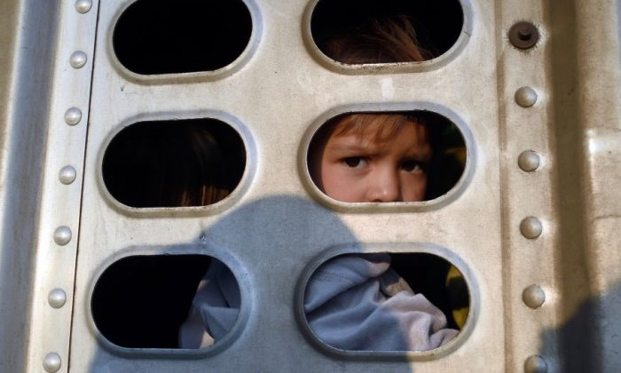 A girl taking part in a migrant caravan looks out from the trailer of a truck along the Irapuato-Guadalajara highway in the Mexican state of Guanajuato, on Nov. 12, 2018. (Alfredo Estrella/AFP/Getty Images)
