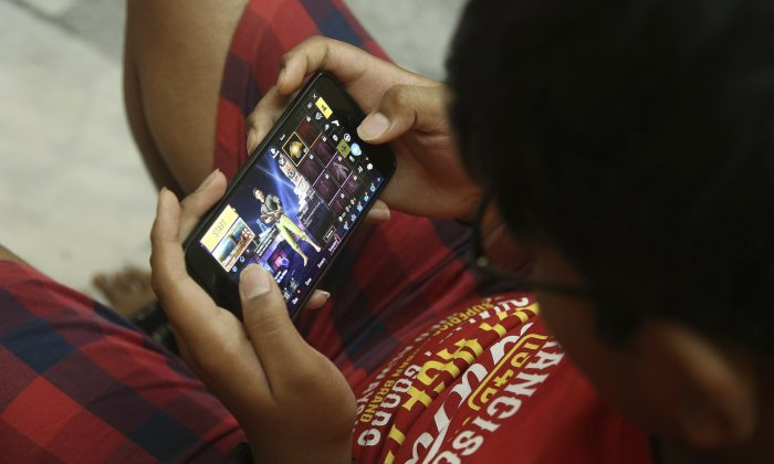 An Indian boy plays an online game PUBG on his mobile phone in Hyderabad, India, on April 5, 2019. (Mahesh Kumar A/Photo via AP)