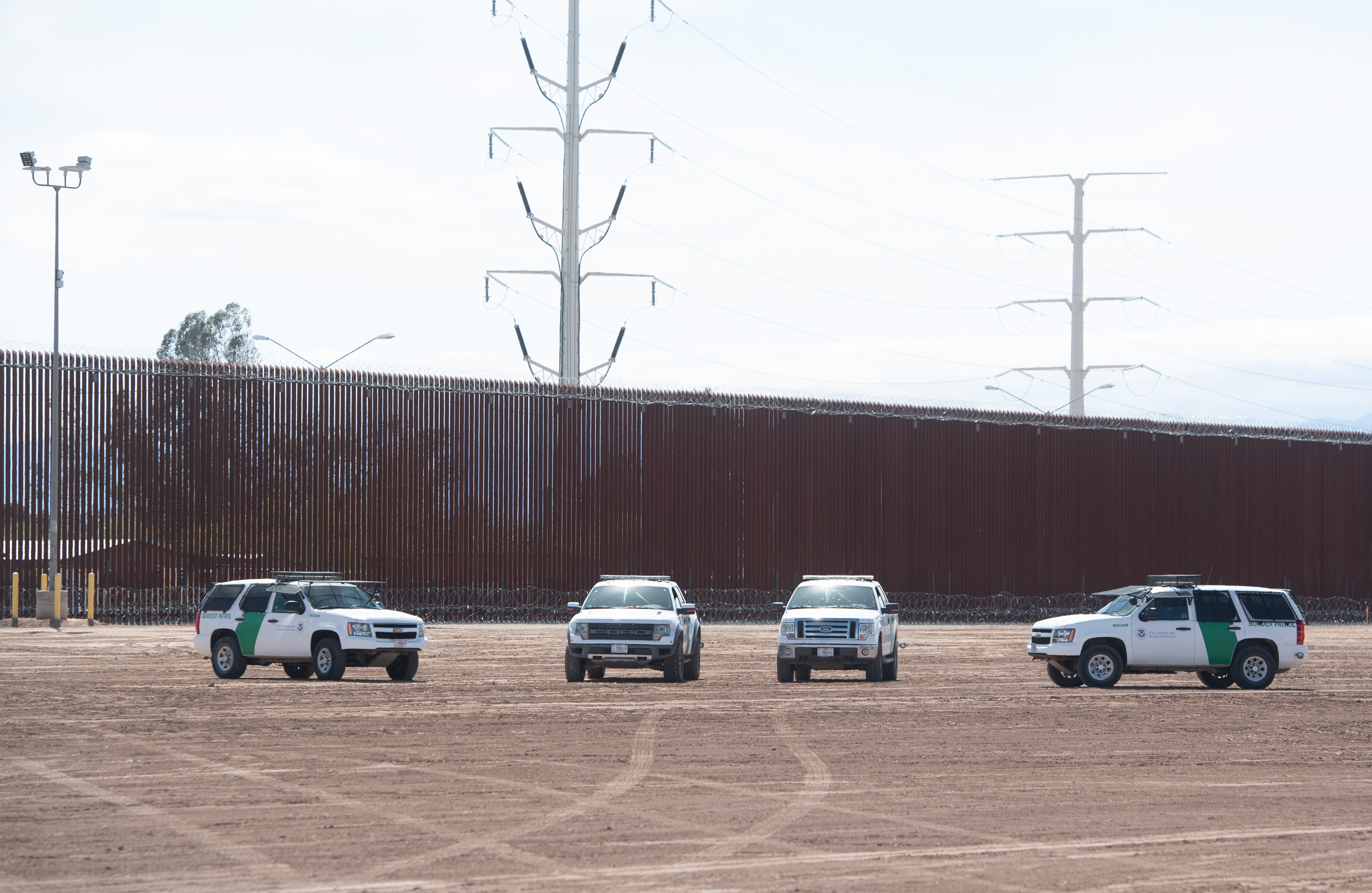 U.S. Customs and Border Patrol cars are seen near the border wall between the United States and Mexico in Calexico