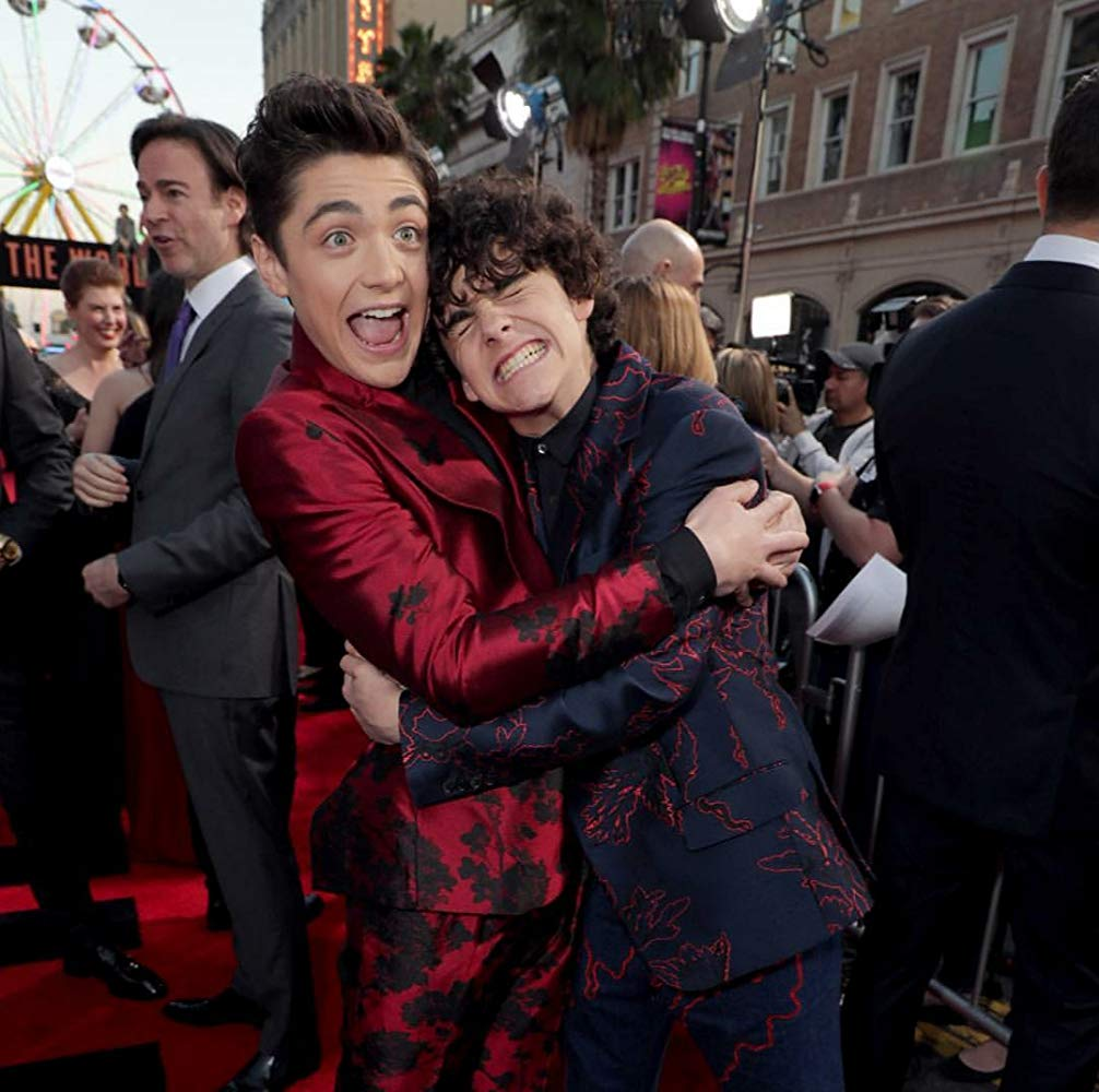 Two boys in suits having a happy hug