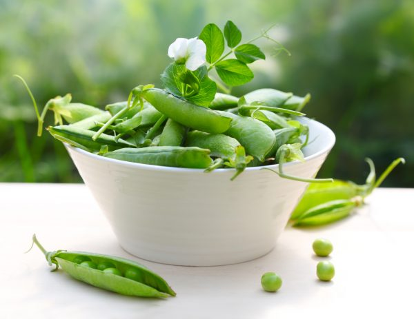 fresh peas in bowl with flower