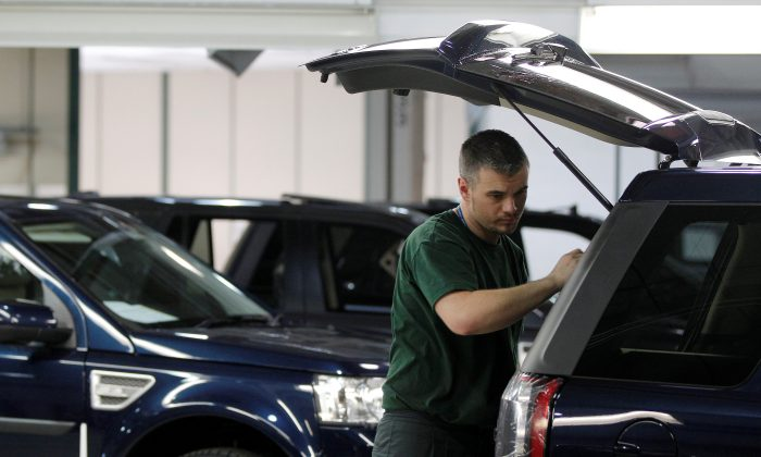 FILE PHOTO: Workers examine Land Rover Freelander vehicles as they come off the production line at Jaguar Land Rover's  Halewood assembly plant in Liverpool, northern England, March 2, 2011. REUTERS/Phil Noble/File Photo