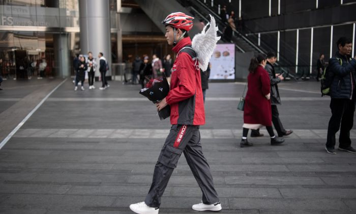 A delivery worker holding a bouquet of flowers and wearing wings poses during a Valentine's day event by Chinese e-commerce company JD.com in Chengdu, China's Sichuan province on February 12, 2019. (FRED DUFOUR/AFP/Getty Images)