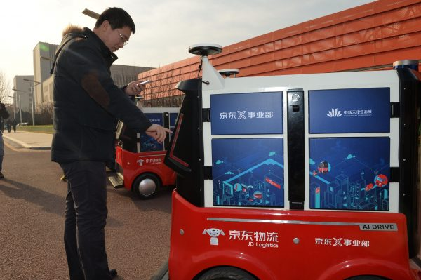 f4ada43aae A man picks up a package from driverless delivery vehicle for Chinese  e-commerce company JD.com during a test operation at the Sino-Singapore  Tianjin ...