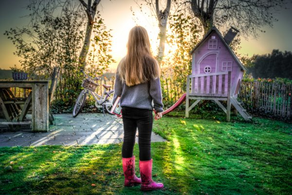girl in backyard playhouse