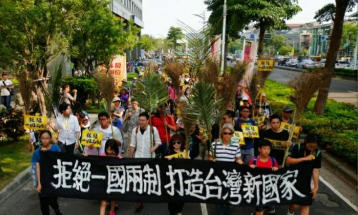 """Protesters raise a banner with the words """"No to 'One Country, Two Systems' and Built a New Taiwan Country"""" in a parade that took place in Kaohsiung, Taiwan, on April 7, 2019. (NTD)"""