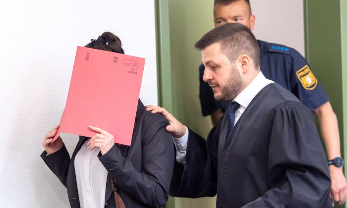 Defendant Jennifer W. (L) hides her face behind a folder and walks next to her lawyer Ali Aydin (R) as she arrives at court for the opening of her trial on April 9, 2019 in Munich, southern Germany. (Peter Kneffel/AFP/Getty Images)