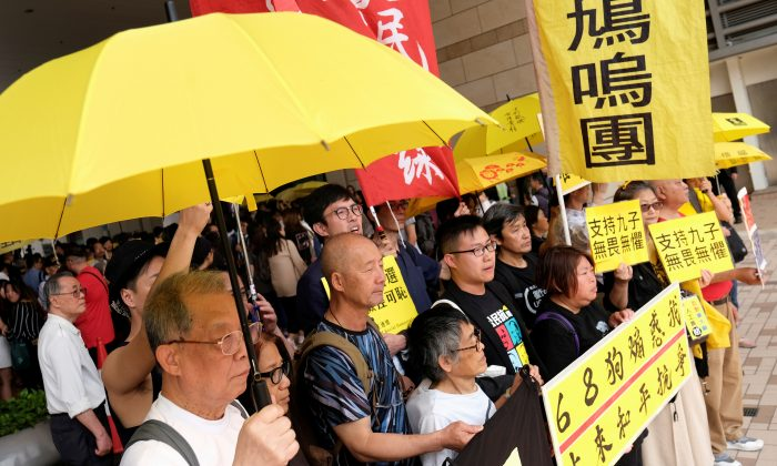 Pro-democracy supporters hold yellow umbrella to support leaders of Occupy Central activists, outside the court, in Hong Kong, China on April 9, 2019. (Tyrone Siu/Reuters)