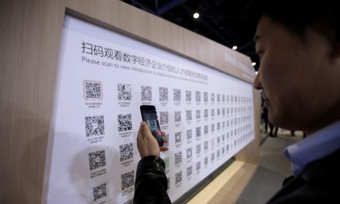 A man uses a mobile phone to scan the QR codes for job-seeking information during an internet expo at the fifth World Internet Conference (WIC) in Wuzhen, Zhejiang Province, China on Nov. 7, 2018. (Jason Lee/Reuters)