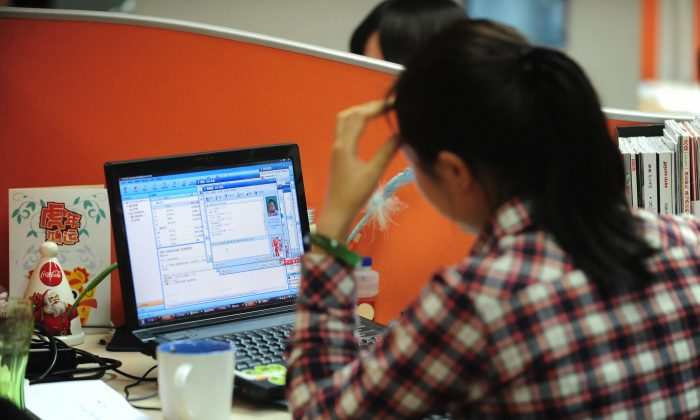 A woman works online in her cubicle at an office in Beijing on February 4, 2010. (FREDERIC J. BROWN/AFP/Getty Images)