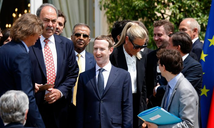 """Facebook's CEO Mark Zuckerberg (C) arrives for a family picture with guests of the """"Tech for Good"""" Summit at the Elysee Palace in Paris, on May 23, 2018. CHARLES PLATIAU/AFP/Getty Images"""