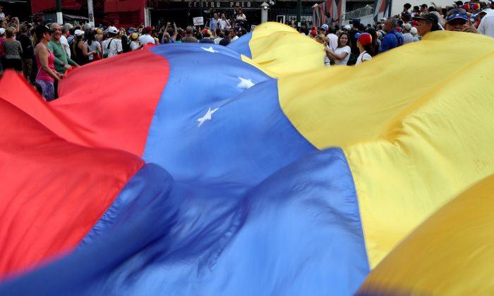 People display a huge Venezuelan flag as they take part in a protest against Venezuelan President Nicolas Maduro's government in Caracas, Venezuela, April 10, 2019. REUTERS/Ivan Alvarado