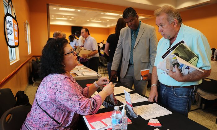 Betty Fernandez (L), from Macy's department store, speaks with Paul Cunningham about job openings during a job fair put on by Miami-Dade County and other sponsors in Miami, Fla., on April 05, 2019. (Joe Raedle/Getty Images)