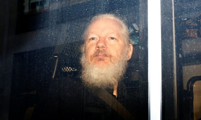 WikiLeaks founder Julian Assange is seen in a police van, after he was arrested by British police, in London on April 11, 2019. (Reuters/Henry Nicholls)