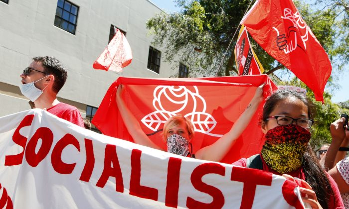 Democratic Socialists of America counter protesters hold signs and flags as they march, protesting an alt-right rally on August 5, 2018 in downtown Berkeley, California. AMY OSBORNE/AFP/Getty Images